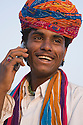 Rajasthani man wearing colorful turban on cell phone; Rajasthan, India --- Model Released