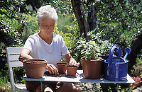 A senior woman potting plants in her garden.