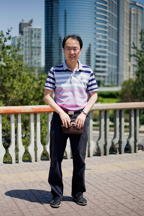 Wanghong, a worker, age 43, poses for a portrait in Beijing. Response to 'What does China mean to you?': 'The center of the world.'  Response to 'What is China's role in the future?': 'A large and modern country.'