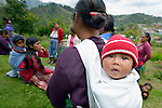 A small child hangs out on its mothers back during a workshop at an eco-agricultural training center in Comitancillo, Guatemala. The center is sponsored by the Maya Mam Association for Investigation and Development (AMMID).