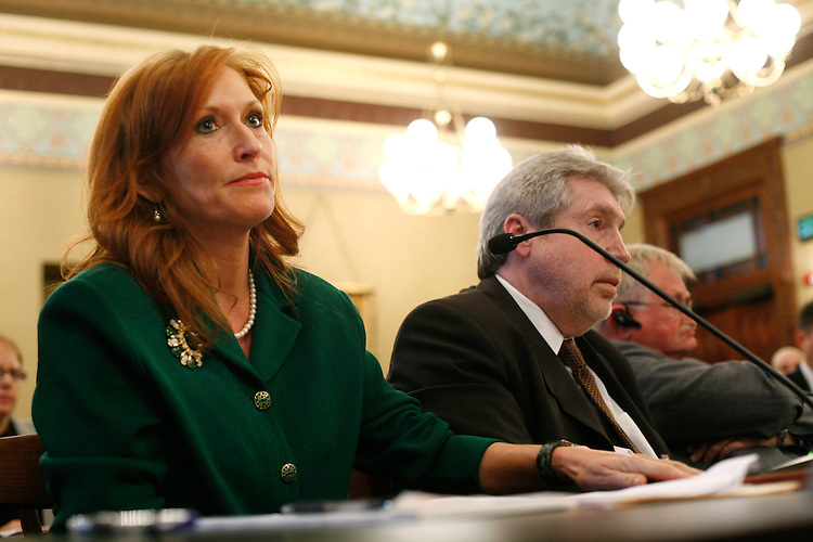 """A new Illinois law passed after former Governor Blagojevich's impeachment for corruption requires that reports from the Governor's Office of Executive Inspector General be made public. It also allows the Illinois Executive Ethics commission to redact some information. As a result, the report explaining why former Illinois Department of Healthcare and Family Services chief of staff Tamara Hoffman was fired in November 2009 was recently released, but all the particulars were omitted. The inspector general said Hoffman engaged in """"decadent behavior,"""" didn't show up for work, and used her state computer for viewing pornography and other personal activity. Here Hoffman presents information during a heated portion of the House impeachment committee hearings for Gov. Rod Blagojevich at the Illinois State Capitol in Springfield, Ill., Dec. 18, 2008. Next to her is Illinois Department of Healthcare and Family Services Director Barry Maram. The inspector general criticized Maram for failing to properly supervise Hoffman."""