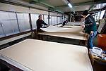Artisans roll dried washi paper produced at Iwano Heizaburo Seijijo in Echizen, Fukui Prefecture, Japan on 21 Feb. 2013. Photographer: Robert Gilhooly