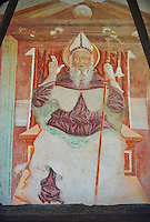 Religious mural of Saint Antonio Abate an a throne above with the canonical symbols of a bell and piglet, above the main portal, Sined by Cristoforo I Baschenis, 1474, on the exterior of the Gothic Church of San Antonio Abate,  Pelugo, Province of Trento, Italy