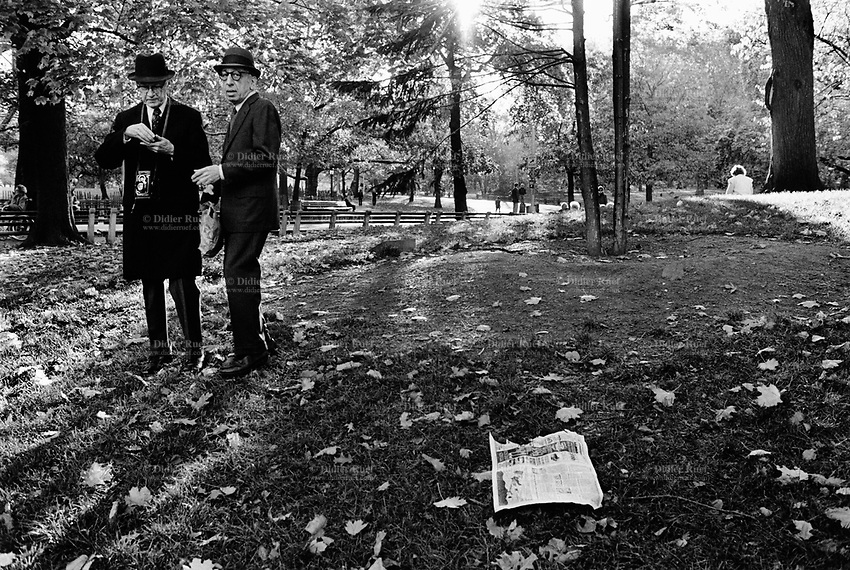 USA. New York. Central Park. Two elderly men are wearing black suits, ties and hats. One is holding a Rolei camera and loads a film. A newspaper lies on the grass. © 1985 Didier Ruef