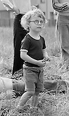 Young lad watching the procession on Festival & Gala Day, Wester Hailes, Scotland, 1979.  John Walmsley was Photographer in Residence at the Education Centre for three weeks in 1979.  The Education Centre was, at the time, Scotland's largest purpose built community High School open all day every day for all ages from primary to adults.  The town of Wester Hailes, a few miles to the south west of Edinburgh, was built in the early 1970s mostly of blocks of flats and high rises.