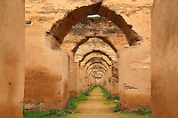 Heri es-Souani, granaries for storing grain and hay and stables for housing 12,000 royal horses, built in the 17th century under Sultan Moulay Ismail Ibn Sharif, 1672-1727, Alaouite dynasty, at Meknes, Meknes-Tafilalet, Morocco. The building has tiny windows, massive walls and a system of underground water channels, which keep the air cool and circulating. Much of the building is now in ruins, although some of the vaults have been restored. Picture by Manuel Cohen