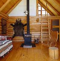 A cast iron wood-burning stove is situated at the centre of the living room in this modern log cabin