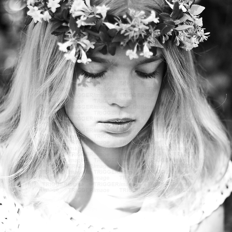 Young girl with blonde hair and floral crown looking down sadly