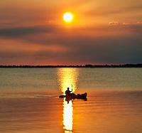 Man kayaking at sunset.