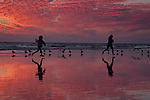 Two girls are captured running with their feet off the ground on the wet sand on Venice Beach at low tide at dusk.