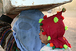 An Afghan refugee woman, with her belongings on her head, awaits transfer from Jalozai refugee camp to a new camp near the Afghan border..