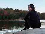 Beautiful smiling asian woman sitting on a rocky shore of lake George, autumn nature scenic, Killarney Provincial Park, Ontario, Canada.