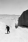 Sunland Park, New Mexico<br /> May 19, 2008<br /> <br /> A US Border Patrol Agent walks along part a new 4 mile stretch of fence recently constructed. He is standing in New Mexico, Texas is the hills in the background and Mexico is on the other side of the fence.
