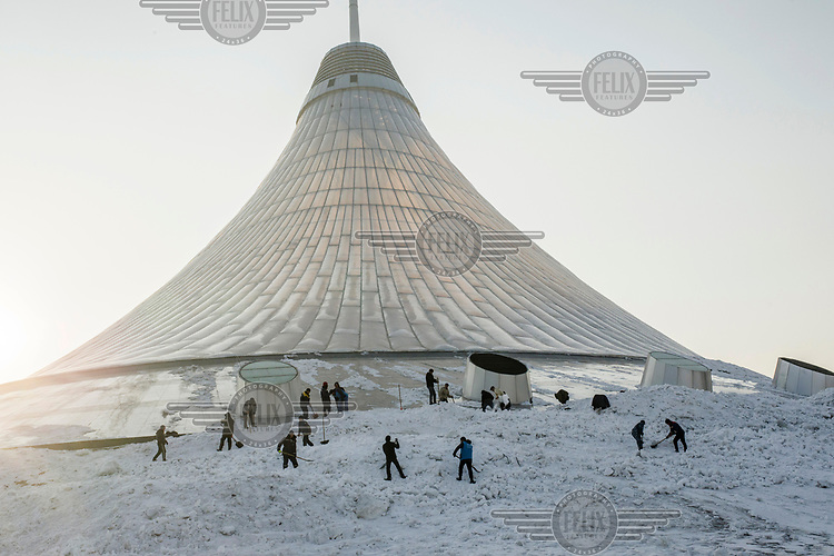 Workers remove snow from the base of the Khan Shatyr shopping centre. The Norman Foster designed mall is in the shape of a traditional nomadic tent and built to withstand winter temperatures of -40 degrees celsius.