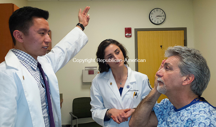 NORTH HAVEN, CT-040914LX01- Quinnipiac University medical students Kevin Kuo, of California and Charissa DiNobile from Rhode Island, both first years examine Paul Dufour, of North Haven, an actor patient the school hires to help train students Wednesday at the Frank Netter School of Medicine at the Quinnipiac University North Haven campus.<br /> Lauresha Xhihani Republican-American