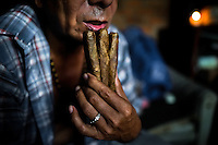A Colombian urban shaman (brujo) worships three cigars before starting the ritual of predicting the future from tobacco in his house in Cali, Colombia, 17 April 2013. Although the original spiritual tradition, kept by the indigenous shamen in Americas for centuries, has been systematically repressed by the Catholic Church, nowadays, more and more people from the urban areas of Latin America discover their roots and consult their everyday problems with esoteric practitioners, healers and shamen. Traditional indigenous rituals (reading of tobacco - interpretation of signs shown by burn tobacco leaves) have merged with European concepts (divination using playing cards) and animistic religious beliefs (worshipping the spirits) brought to Americas by the African slaves, keeping the spirituality in modern Latin American society alive.