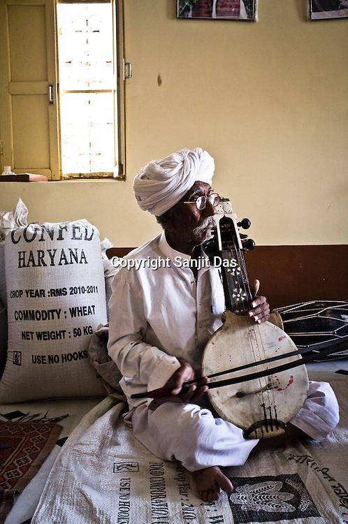 75-year-old Manganiyar artist and a Padmashree awardee, Saqar Khan plays his Kamancha (music instrument) during field recordings inside his house in Hamira village of Jaiselmer district in Rajasthan, India. Photo: Sanjit Das/Panos