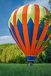 Hot air balloons float over a field at the Quechee Balloon Fest in Quechee, VT