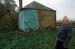 Great Tew Oxfordshire 1980s. Local resident Frank Salt who lives n the Toll House. Rxterior Toll House showing damage.