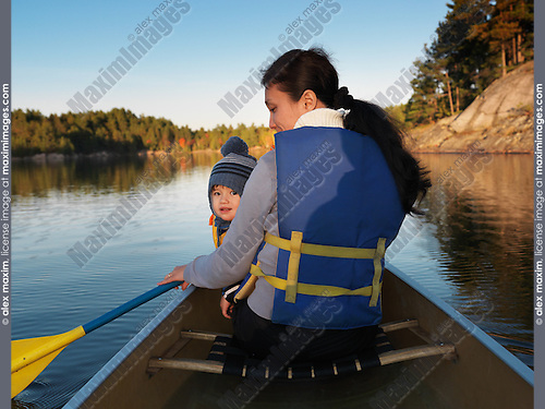 Woman in a canoe with a child. Sunset fall nature scenery. Paddling in Killarney Provincial Park, Ontario, Canada.