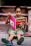 India, Calcutta..YOung girl siting on the street reading Cinderella on the street waiting for her father to finish work - as a street shoe-repairer..