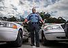 Houston ISD Police Corporal James Harding poses for a photograph with patrol vehicles, May 20, 2014.