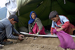 Following an October 8, 2005, earthquake, these homeless boys help their mother clean out their tent in a camp outside Balakot sponsored by Church World Service/Action by Churches Together.