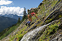 WA11038-00...WASHINGTON - Hiker crossing a steep slope on the Bailey Range Traverse in Olympic National Park. (MR# S1)