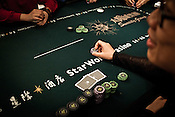 A poker player places his chips on the poker table at the Galaxy Macau Hotel in Macau, China.
