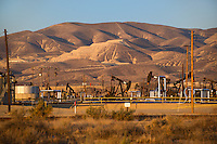 730850356 oil derricks and storage tanks in a working oil field in southern kern county california
