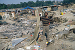 PRIMROSE, SOUTH AFRICA - MAY 23: Rasta, (l) a bricklayer, collects rubble after a shack fire on May 23, 2008 at Marathon squatter camp outside Johannesburg, South Africa. He was one of the South Africans that chased out African immigrants in the area. Several shacks were burned down next to his. A man was burned alive down the street and thousands of people fled to a nearby police station for safety. South Africa was hit by xenophobic attacks that killed about sixty people and displaced tens of thousands of people. (Photo by: Per-Anders Pettersson/Getty Images).