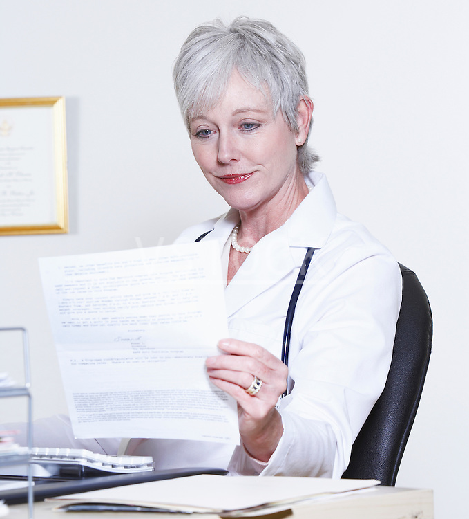 Usa California Fairfax Female Doctor Reading At Desk