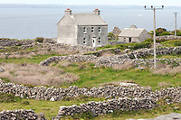 Farm House and stone walls, Inis Mór, Aaran Islands, County Galway, Ireland..The island of Inis Mór ( meaning the big island) is one of the most popular tourist destinations in Ireland. The islands inland landscape of uniquely blanketed rock surface are glazed with man made rock walls that meander and cross all directions as far as one can see. Well known internationally, it is steeped in history and resembles an outdoor museum with over 50 different monuments of Christian, pre Christian and Celtic mythological heritage. Picture James Horan