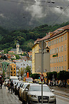 Taxi rank with pastel coloured buildings and shops in the city, showing forests, church and clouds. Innsbruck, Austria.
