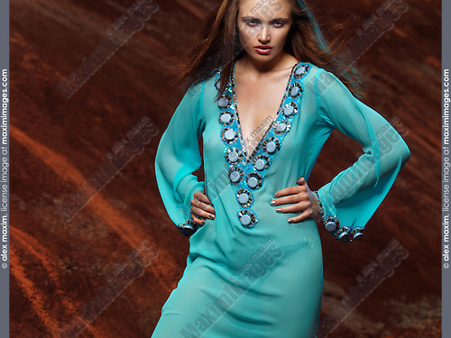 Young woman fashion model wearing blue sheer caftan dress at exotic location