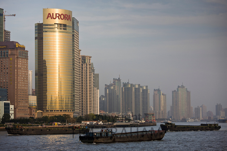View of barges on Huangpu River and the Aurora tower in Pudong financial district from the Bund, Shanghai, China