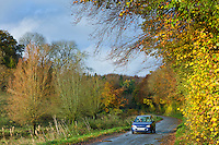 Small saloon car driven along country lane in Autumn, The Cotswolds, UK