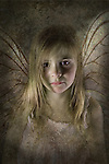 Young fairy child with wings looking sad and desolate directly at the camera