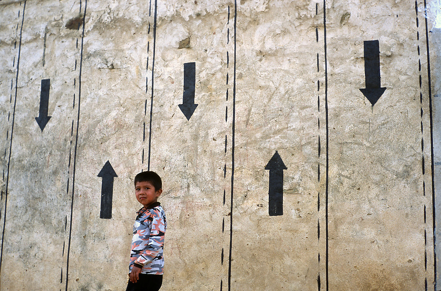 """A boy walks below artfully painted walls in the village of Pucara (acute accent on final a), Bolivia. Ernesto """"Che"""" Guevara was captured by the Bolivian army in 1967 in a nearby valley and executed in nearby La Higuera days later. Guevara and fellow communist guerillas were attempting to launch a continent-wide revolution modeled on Guevara's success in Cuba in the late 1950s. The Bolivian government recently began promoting the area where he fought, was captured, killed and burried for 30 years as the """"Ruta del Che,"""" or Che's Route. (Kevin Moloney for the New York Times)"""