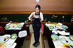 """Staffer Natsumi Takagi takes a break for a bite to eat before guests arrive to board the Kachidoki """"yakata-bune"""" pleasure boat, one of five operated by the Yasuda family's company Harumiya Co. in Tokyo, Japan on 31 August  2010. Photographer: Robert Gilhooly"""