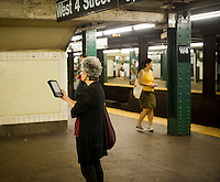 A woman with her Amazon Kindle electronic book reader waits for a train in a subway station in New York on Sunday, September 25, 2011. (© Richard B. Levine)