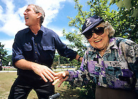 04 Jul 1999, New Hampshire, USA --- Republican presidential candidate George W Bush greets a senior citizen outside a retirement home while marching in a July 4th parade in New Hampshire. | Location: Amherst, NH.  --- Image by © Brooks Kraft/Corbis