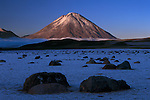 Icy morning sunlight illuminates a volcano while surrounding plain remains in shadow