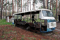 On April 26,1986, an explosion at Ukraine's Chernobyl Nuclear Power Plant changed history, sending radiation and political shockwaves across Europe. Nearby towns and villages were first evacuated, then abandoned. Vehicles used for evacuation and decontamination became too radioactive to keep. This abandoned bus, stripped of parts, rusts away in the forest near Lyutezh, Ukraine.  <br /> ------------------- <br /> This photograph is part of Michael Forster Rothbart's After Chernobyl documentary photography project.<br /> &copy; Michael Forster Rothbart 2007-2010.<br /> www.afterchernobyl.com<br /> www.mfrphoto.com <br /> 607-267-4893 o 607-432-5984<br /> 5 Draper St, Oneonta, NY 13820<br /> 86 Three Mile Pond Rd, Vassalboro, ME 04989<br /> info@mfrphoto.com<br /> Photo by: Michael Forster Rothbart<br /> Date:  5/2007    File#:  Canon 20D digital camera frame 6582<br /> ------------------- <br /> Original caption: .Photo title:.Abandoned bus in Lyutezh..Caption:.Many vehicles used for evacuation and decontamination were too radioactive to keep using after the Chernobyl accident. Trucks, busses and contaminated equipment were buried in over 800 dumpsites, mostly unmarked. Other machinery was simply abandoned. These have since been stripped of any salable parts by scrap metal dealers...Outside the restricted Exclusion Zone are 2,293 small villages in Ukraine where the land was slightly contaminated by radioactive fallout. Those who still live here receive very little information about possible health risks. Many receive small government pensions for their status as Chernobyl survivors...Quote: none.-------------------
