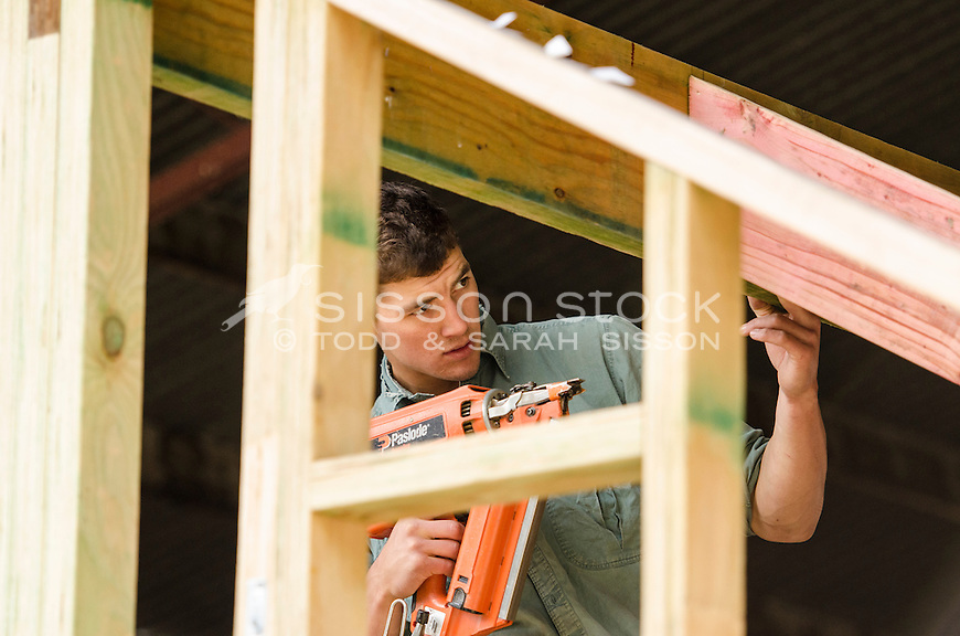 Young builder using nail gun on timber house frame, New Zealand - stock photo, canvas, fine art print