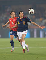 Midfielder Sergio Busquets is shadowed by Chile's Jorge Valdivia as both pursue a loose ball. Spain won Group H following a 2-1 defeat of Chile in Pretoria's Loftus Versfeld Stadium, Friday, June 25th, at the 2010 FIFA World Cup in South Africa..