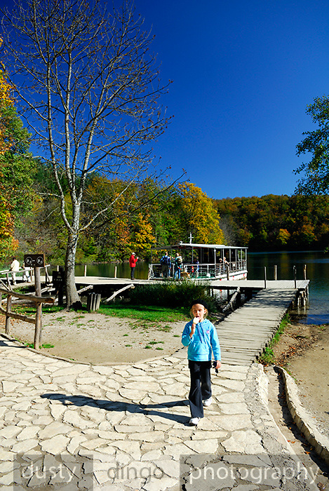 Child eating ice-cream, walking toward camera, away from boat on lake. Plitvice National Park, Croatia
