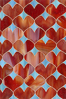 Hearts, a glass waterjet mosaic  shown in Garnet and George, is part of the Erin Adams Collection for New Ravenna Mosaics.<br />