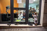 Un bambino italiano guarda incuriosito gli uomini che pregano dentro un negozio di immigrati del Bangladesh, prima del Iftar, la cena che rompe il digiuno nel mese del Ramadan. Roma 18 Agosto 2011<br /> Italian baby look intrigued  men praying inside a shop of migrants from Bangladesh, before the Iftar, the meal that breaks the fast during the month of Ramadan.<br />  August 18,2011 in Rome,Italy.