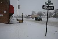 Detroit: paesaggio urbano in inverno. Un'automobile fuoristrada percorre la carreggiata innevata. Intorno case e negozi. Un cartello stradale indica il nome della via e il senso unico.